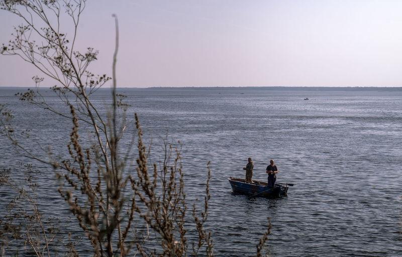 Men in sea against sky