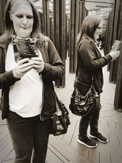 Mature Woman Holding Mobile Phone While Standing In Mirror Maze
