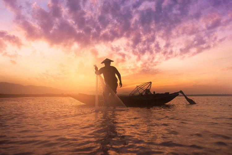 Fisherman casting net in lake against sky during sunset