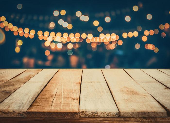 Boardwalk against defocused image of illuminated lights at night