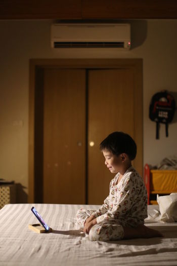 Side view of a boy sitting at home