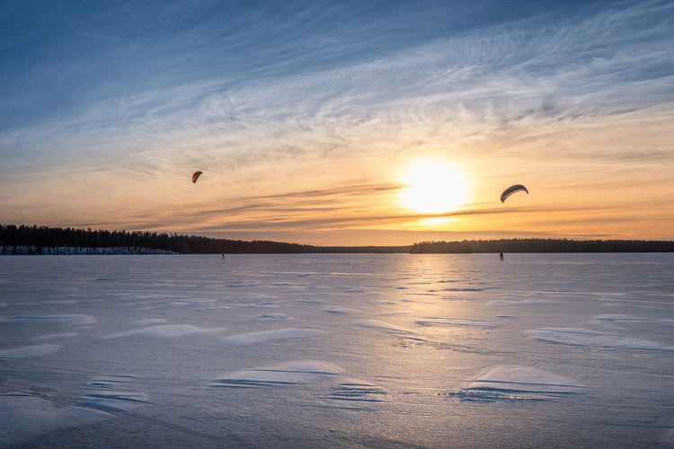 Kite skiing on frozen lake with beautiful sunset at winter evening in Finland Sky Sunset Beauty In Nature Scenics - Nature Tranquility Tranquil Scene Orange Color No People Outdoors Cloud - Sky Flying Nature Sun Finland Extreme Sports Kite Kite Skiing Skiing Landscape Tranquility Beauty In Nature Winter Cold Temperature Mood Bright