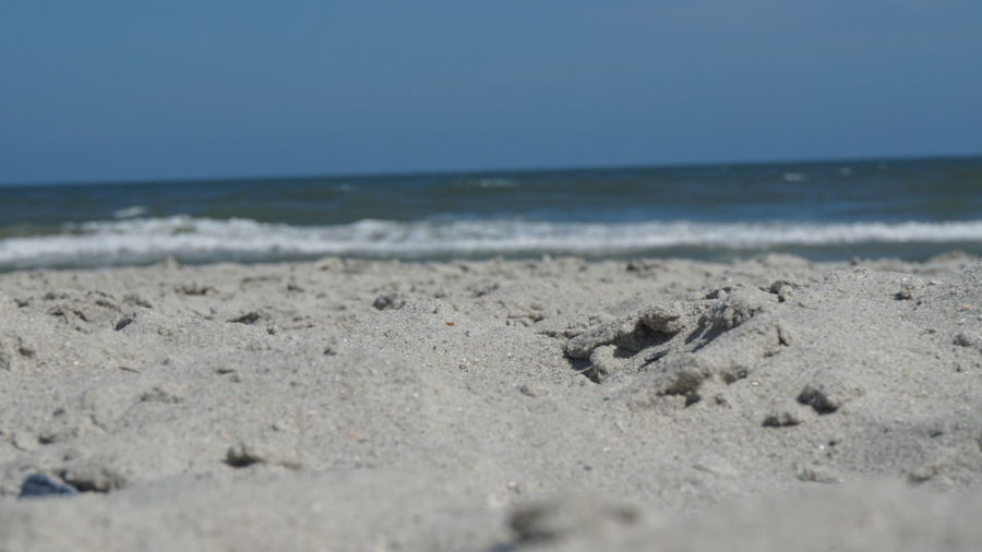 Close-up of sand on beach against clear sky