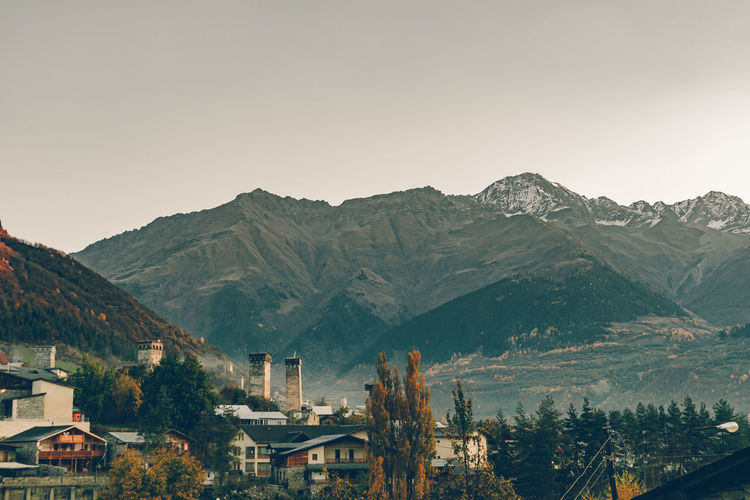 Townscape by mountains against clear sky