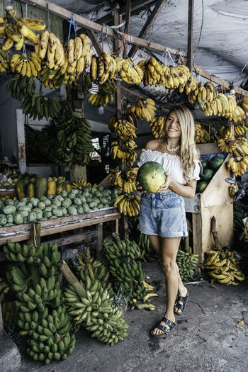 Full length of smiling woman standing at market stall