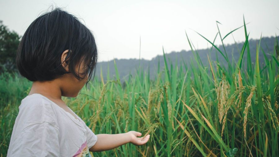Side view of girl touching plants on field against sky