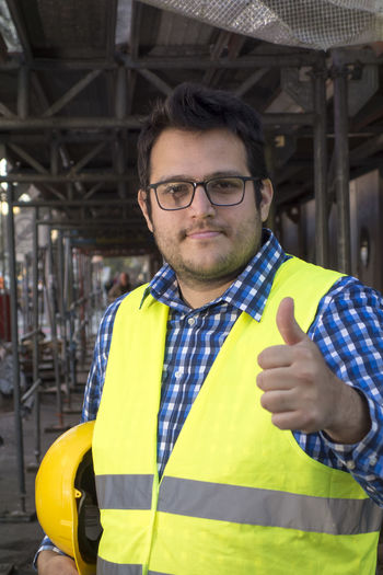 Positive and successful young construction worker posing showing thumbs up gesture. outdoors