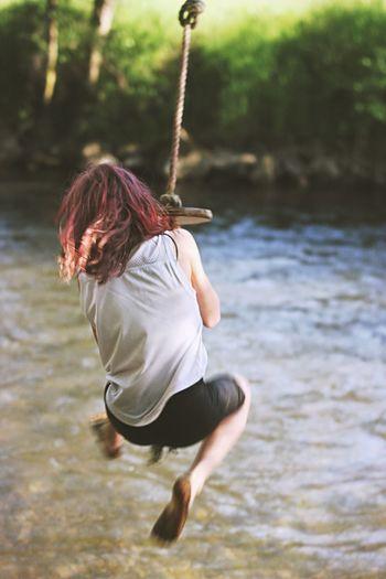 Woman swinging over lake
