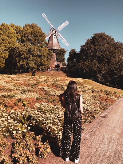 Rear view of woman standing on footpath against traditional windmill