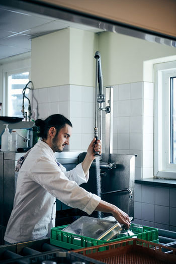 Side view of man working in kitchen