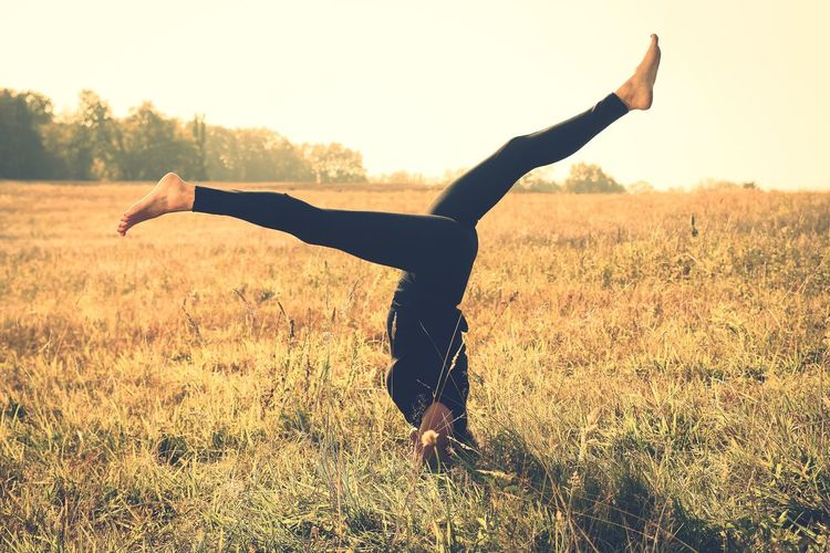 Side view of woman doing handstand on grassy field during sunny day
