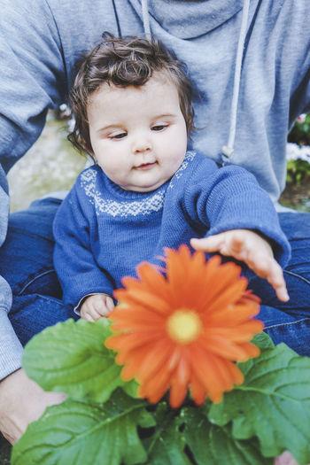 Full length of cute baby girl on flowering plant