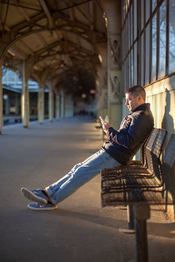 Sitting One Person Full Length Architecture Men Seat Young Adult Side View Young Men Casual Clothing Real People Lifestyles Communication Leisure Activity Sunlight Day Built Structure City Shadow Outdoors Teenager Railway Station Station Railway Waiting