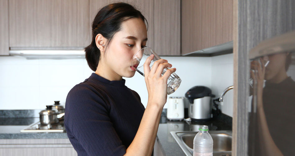 Mid adult woman holding drink at home