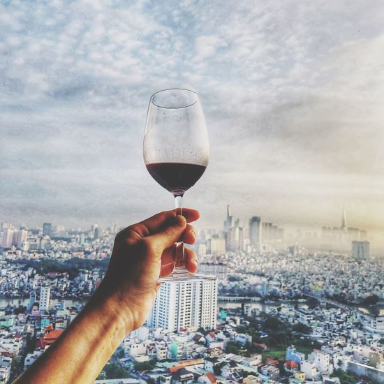 Cropped hand of man holding wineglass against cityscape