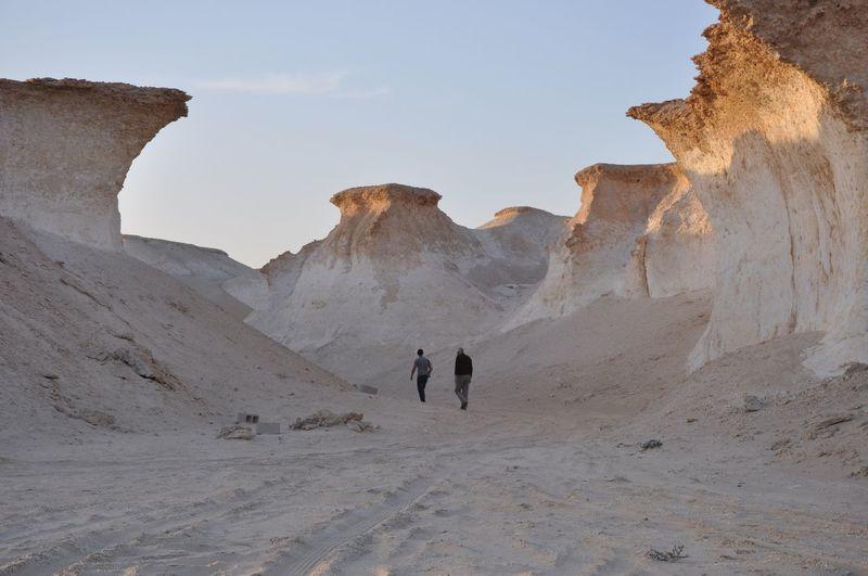Rear View Of Tourist Walking Amidst Sandstones
