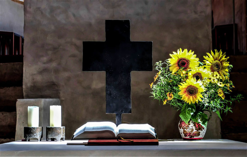 Close-up of flower vase and bible on table