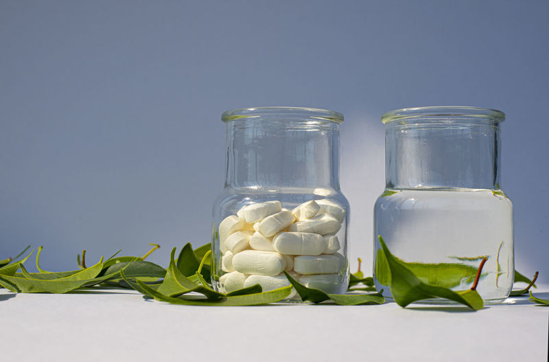 Close-up of glass jar with bottle against white background