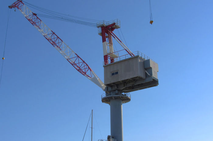 Port crane in Livorno, Italy Action Blue Sky Commercial Dock Construction Crane Development Harbor Heavy Hoisting Hook Industrial Crane Industry Large Loading Low Angle View Machine Metal Picking Up Pier Service Shipyard Sky Steel Tall Unloading