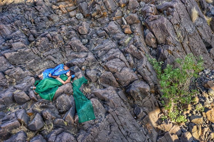 High Angle View Of Couple Lying On Rock Formation