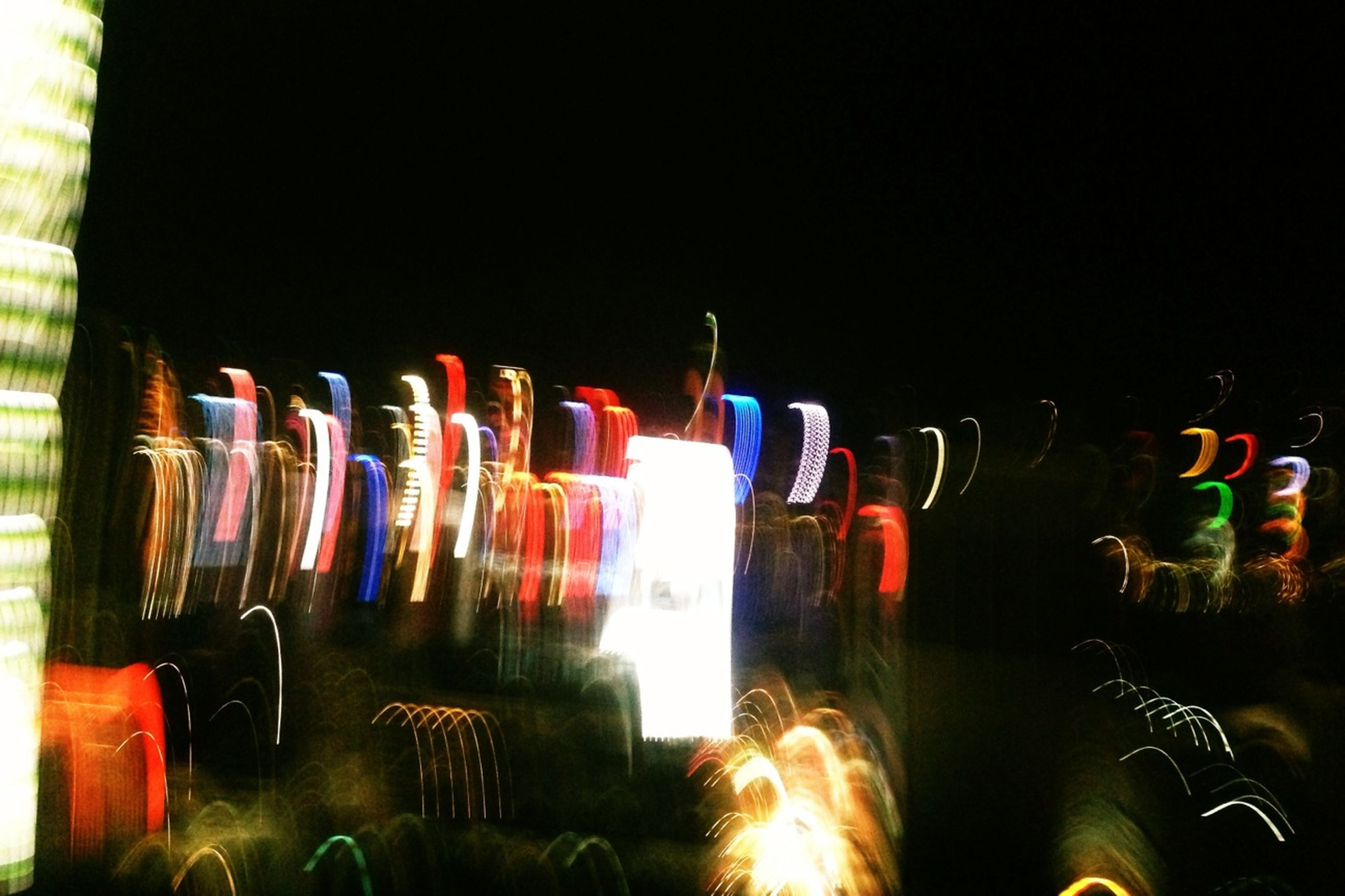 night, illuminated, multi colored, long exposure, reflection, motion, glowing, building exterior, light - natural phenomenon, water, blurred motion, copy space, built structure, burning, no people, fire - natural phenomenon, architecture, outdoors, in a row, arts culture and entertainment