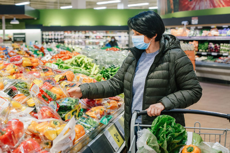 Grocery shopping. middle age woman in protective face mask buying food vegetables in supermarket