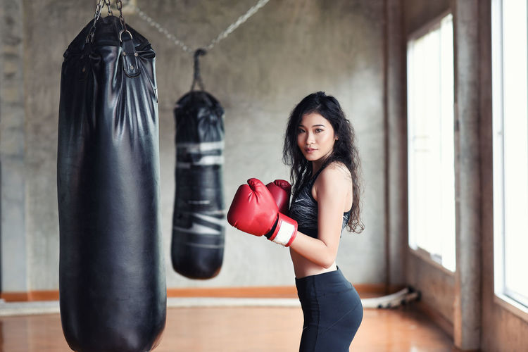 Portrait of young woman practicing with punching bag in studio