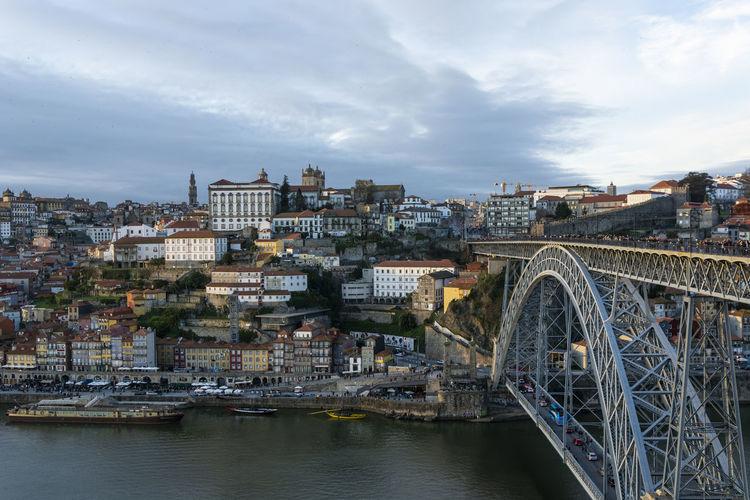 Bridge over river by buildings in city against sky