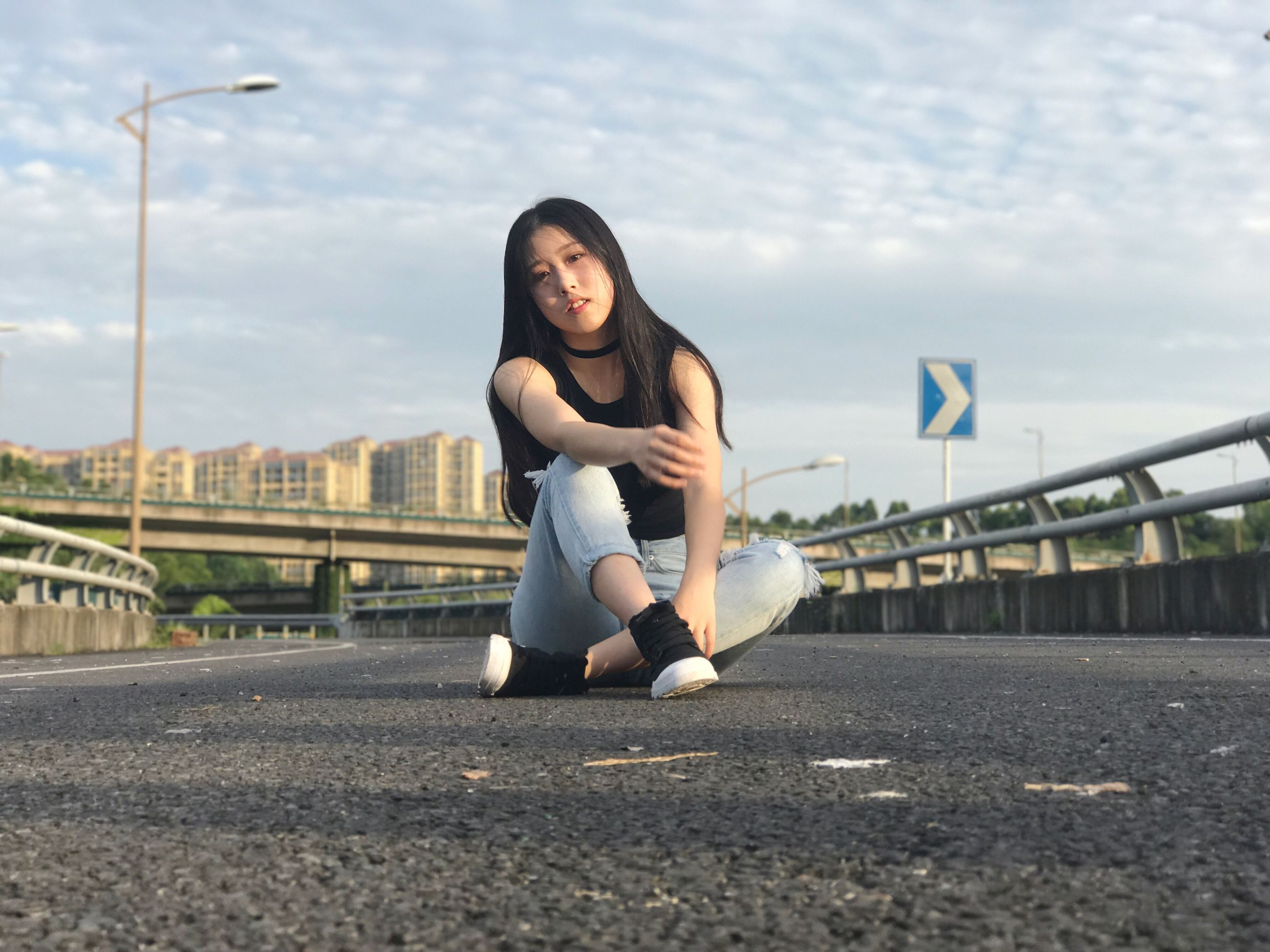 lifestyles, bridge - man made structure, one person, young adult, real people, leisure activity, young women, outdoors, built structure, day, healthy lifestyle, sky, full length, sports clothing, cloud - sky, architecture, sitting, exercising, beautiful woman, sport, city, people