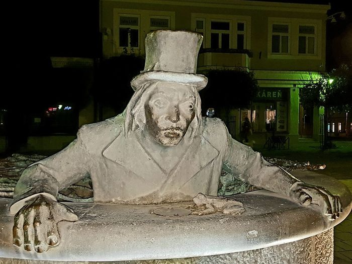Statue against fountain in city at night