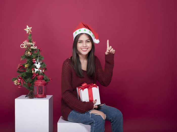 Portrait of smiling woman with gifts and decorations against red background during christmas
