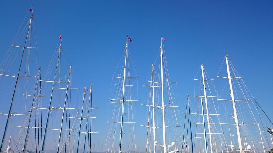 Low Angle View Of Boat Mast Against Clear Blue Sky