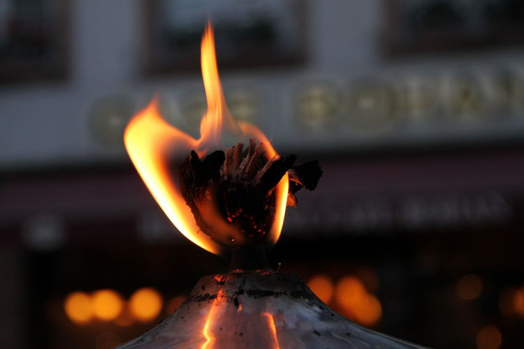 Close-up of lit candle burning in temple