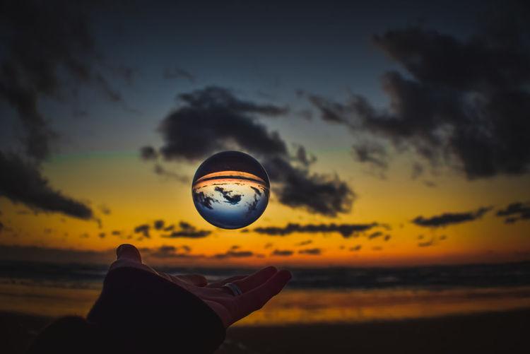 Silhouette man holding ball against orange sky