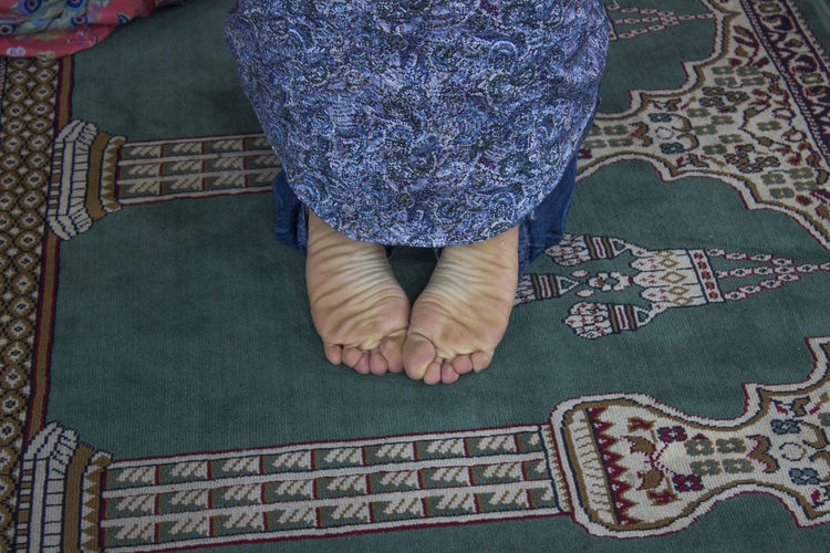 Low Section Of Person Kneeling On Carpet