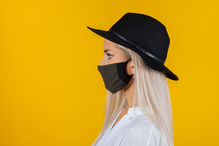 Close-up of woman wearing mask and hat against yellow background