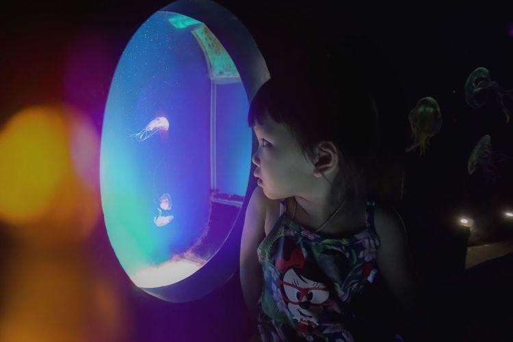 Portrait of girl looking at illuminated nightclub