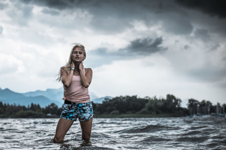Young woman standing in lake against cloudy sky
