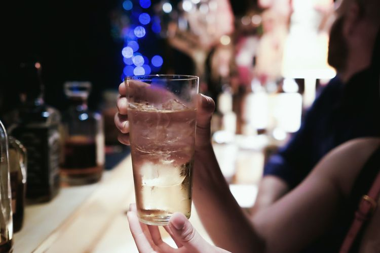 Cropped image of woman holding drink in bar