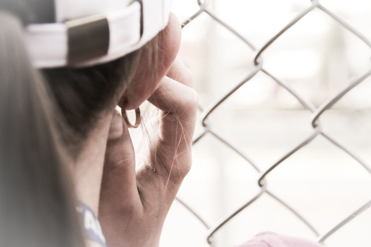 Protecting her hears from a loud noise One Person Body Part People Portrait Earring  Ear Ring Hat Noise White Color Noice Loud Fingers Ear Fence Portrait Photography Portrait Of A Woman
