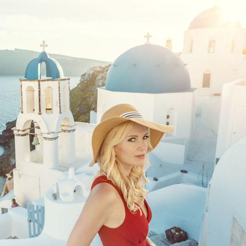 Portrait of woman wearing hat against built structure
