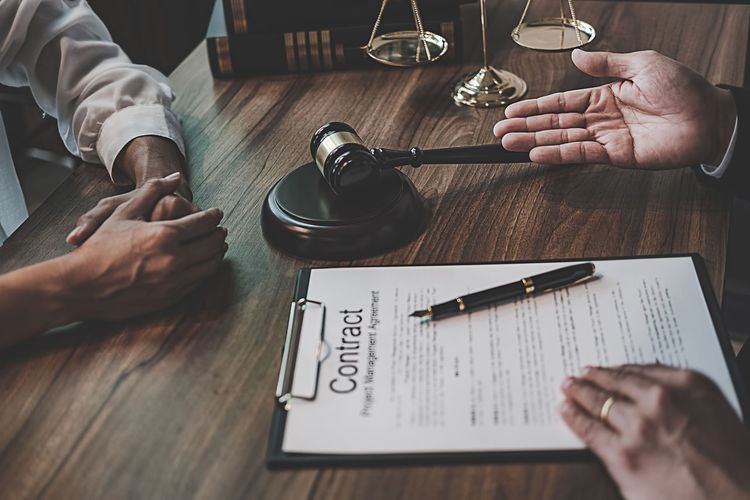 Judge gesturing while sitting with client at table in office