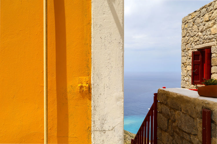 Yellow building by sea against sky