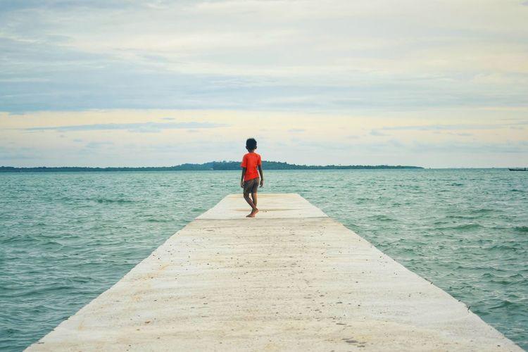 Rear View Of Boy Walking On Pier Over Sea Against Sky