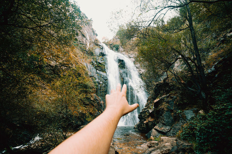 Cropped image of person against waterfall in forest