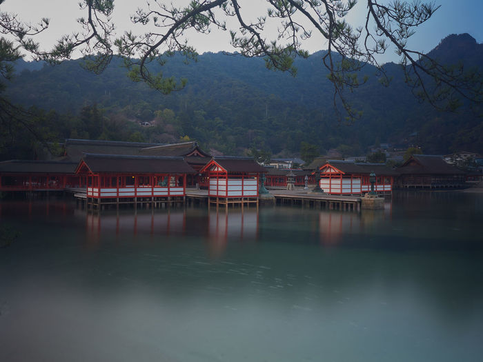 Japanese shrine by lake and mountains against sky