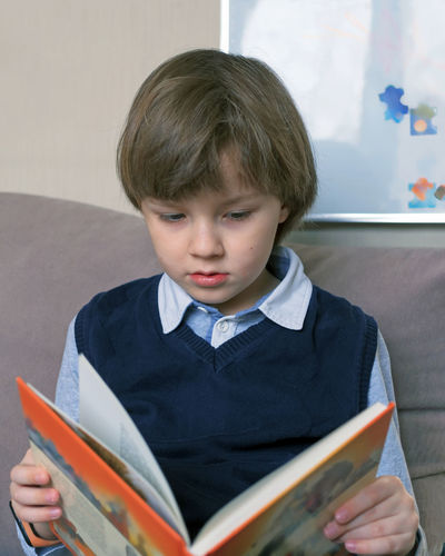 Cute boy reading book sitting on sofa at home