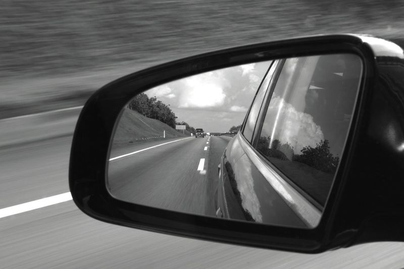 Speeding in a Car on a Highway in Malaysia . The Road Wizzing By and the Rearview Mirror gives a Last Glimpse of what Passed By. Still Life
