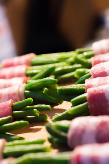 Close-Up Of Bacon Beans Wraps On Cutting Board