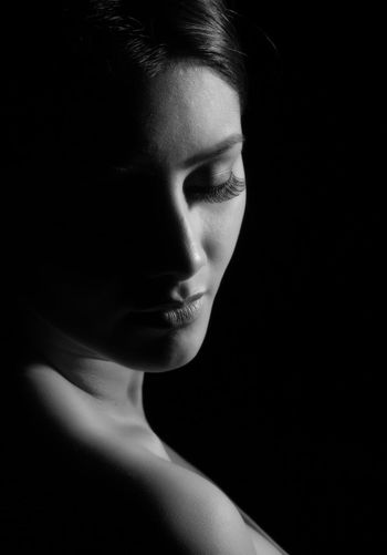 Close-up of woman looking away over black background